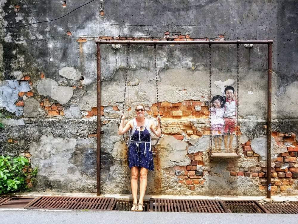 Posing with a famous piece of Georgetown's street art . Try to find them all!