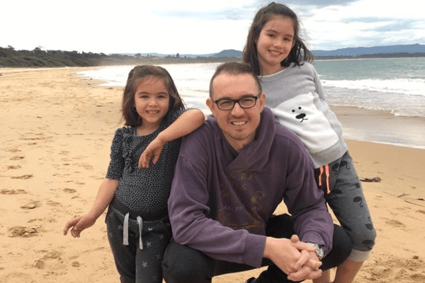 Andrew McGuire and his two daughters at the beach.