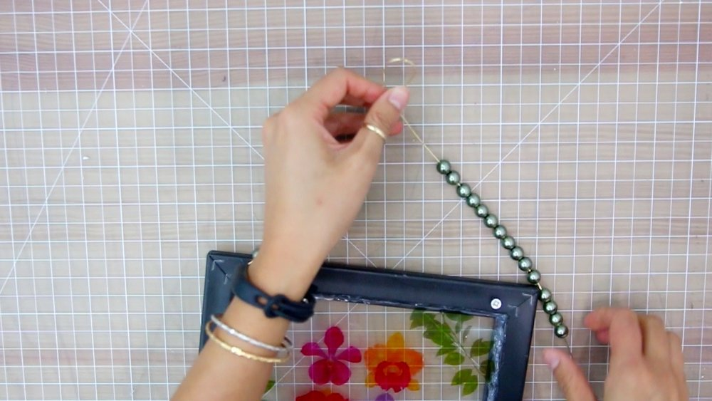 Find the mid-point of the wire, and equally distribute the beads onto each side of the mid -point and make a twist to create a loop at the top.