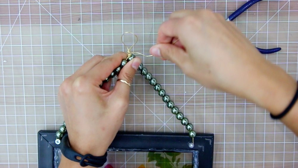 Use the excess wire to wrap the loop at the midpoint to give it a final finish.