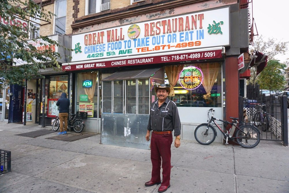 New York is a Mexican Cowboy walking through Sunset Park in front of a Chinese Take Out