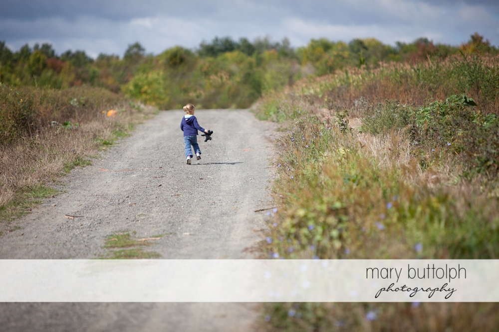 Girl with her doll running on the road at Tim's Pumpkin Patch