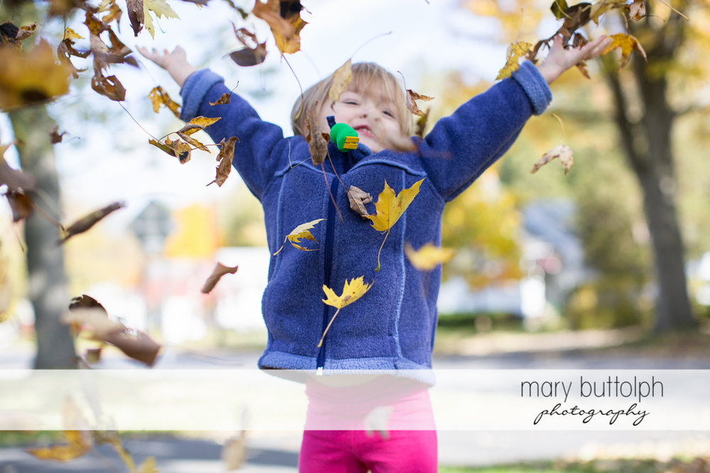 Girl playing with the leaves in the yard at Skaneateles