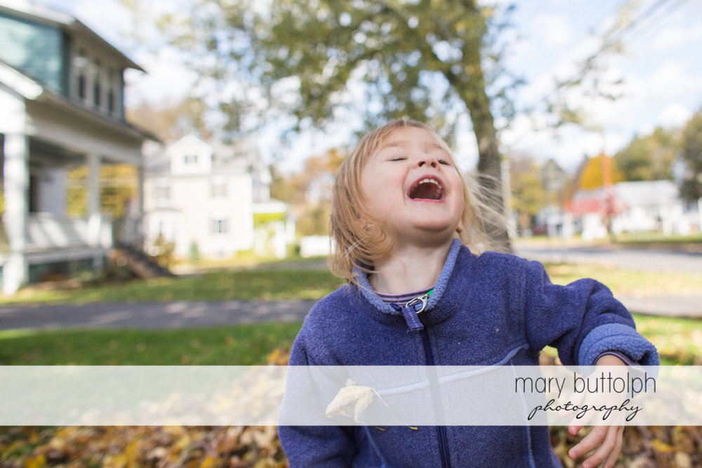 Girl laughing in the yard in front of her home at Skaneateles