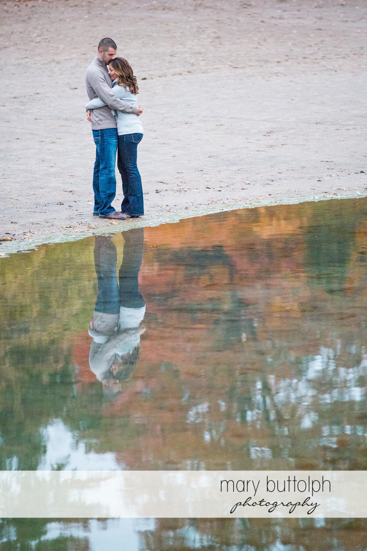 Couple embrace near the lake at Skaneateles Engagement