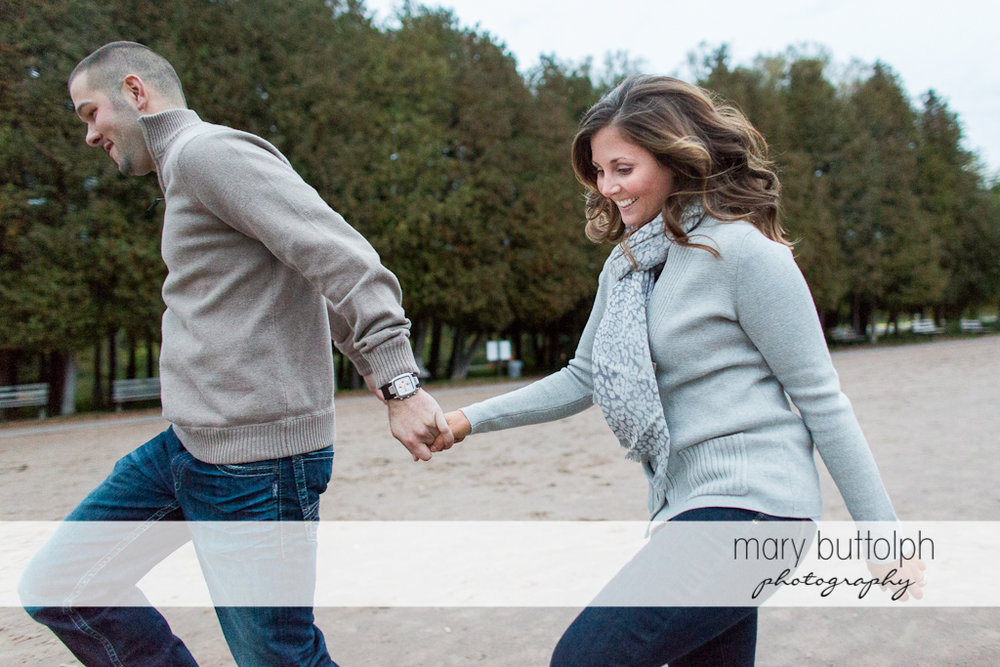 Couple frolic in the park at Skaneateles Engagement