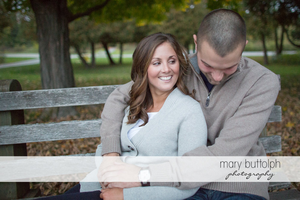 Couple sit on a bench in the park at Skaneateles Engagement