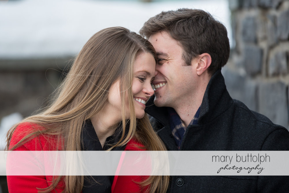 Couple share a tender moment in front of a brick wall at Skaneateles Engagement