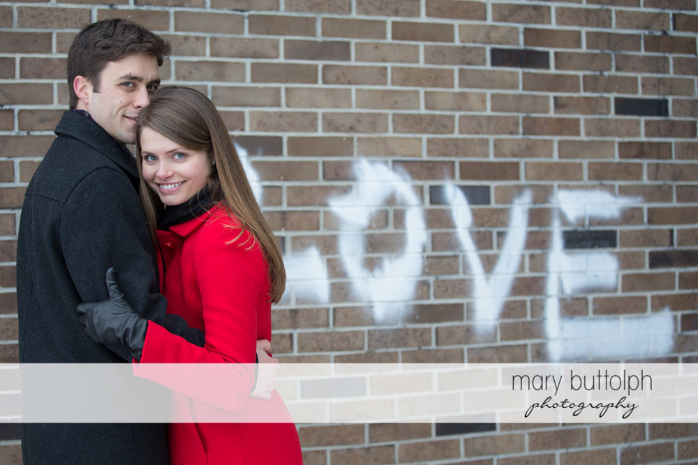 "Couple stand in front of a brick wall with the word ""Love"" at Skaneateles Engagement"