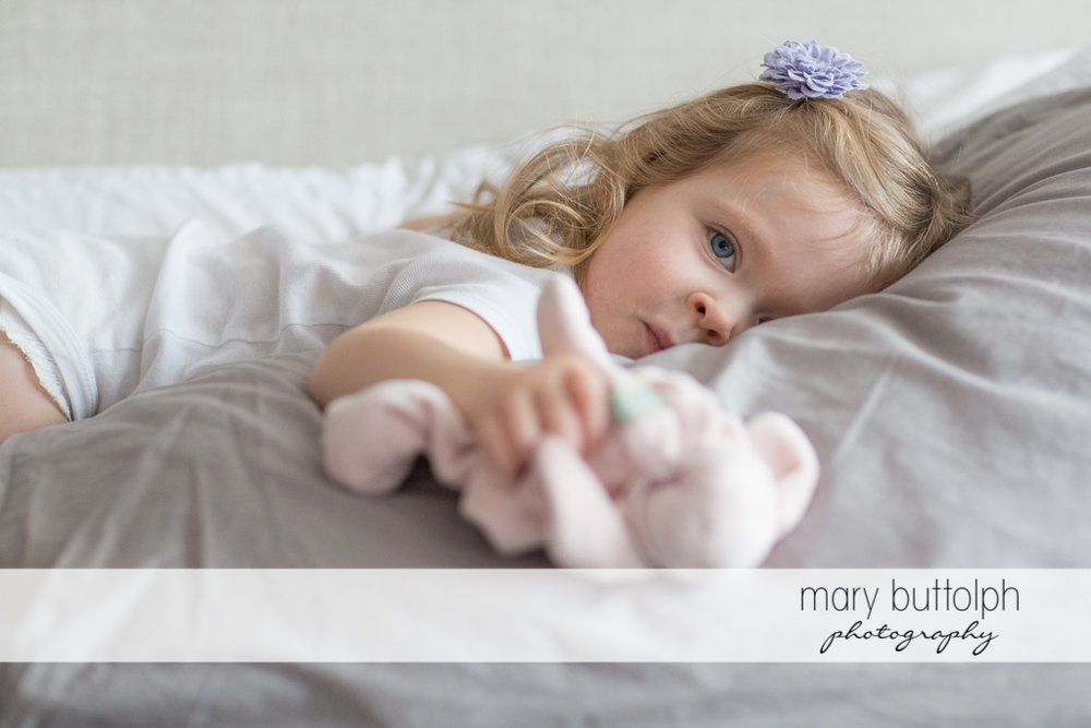 Girl tries her best not to sleep in bed during the photo shoot at Skaneateles Newborn Photography