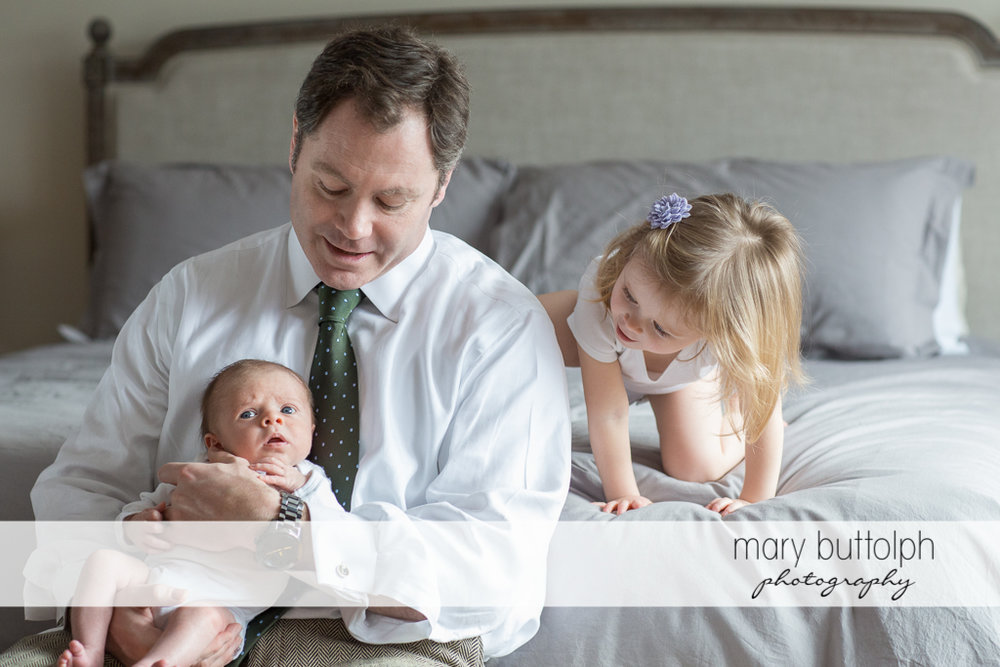 Baby boy looks surprised while his dad and sister are amused at Skaneateles Newborn Photography