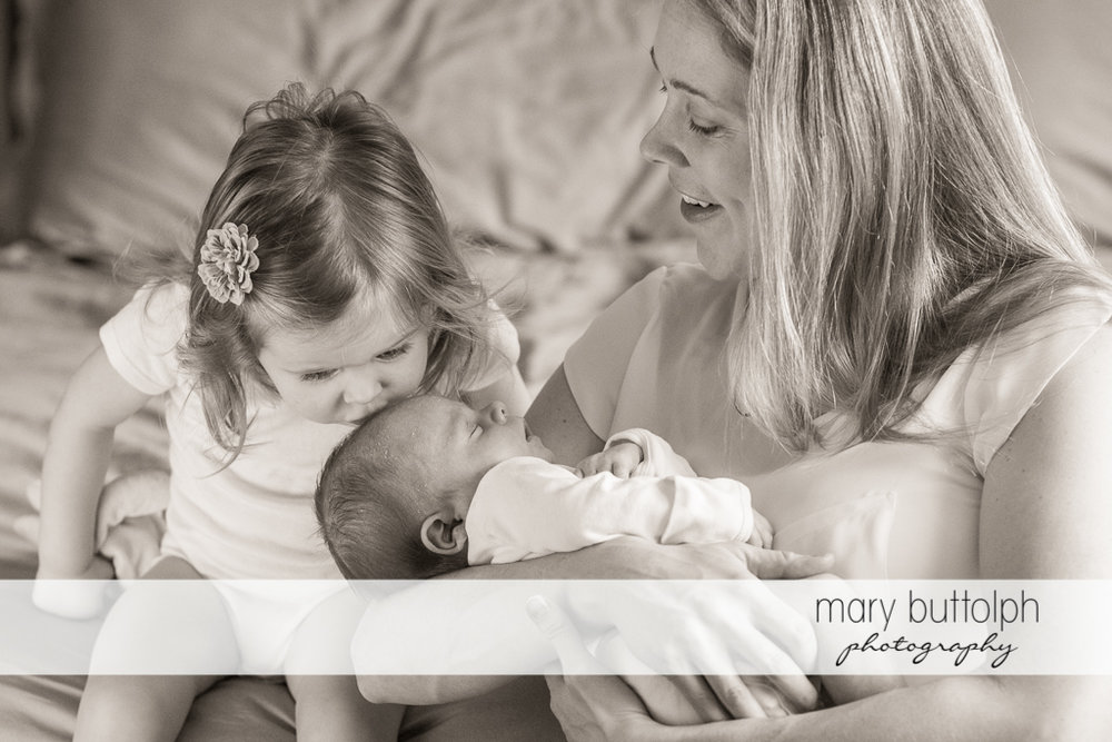 Woman seems amused that her daughter is kissing the new baby at Skaneateles Newborn Photography