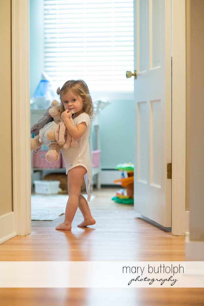 Girl carrying her favorite stuffed animals pauses at the entrance to her bedroom at Skaneateles Newborn Photography