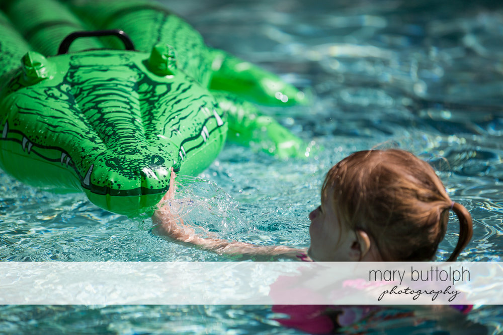 Girl plays with her alligator float in the pool at Sanibel Island Vacation