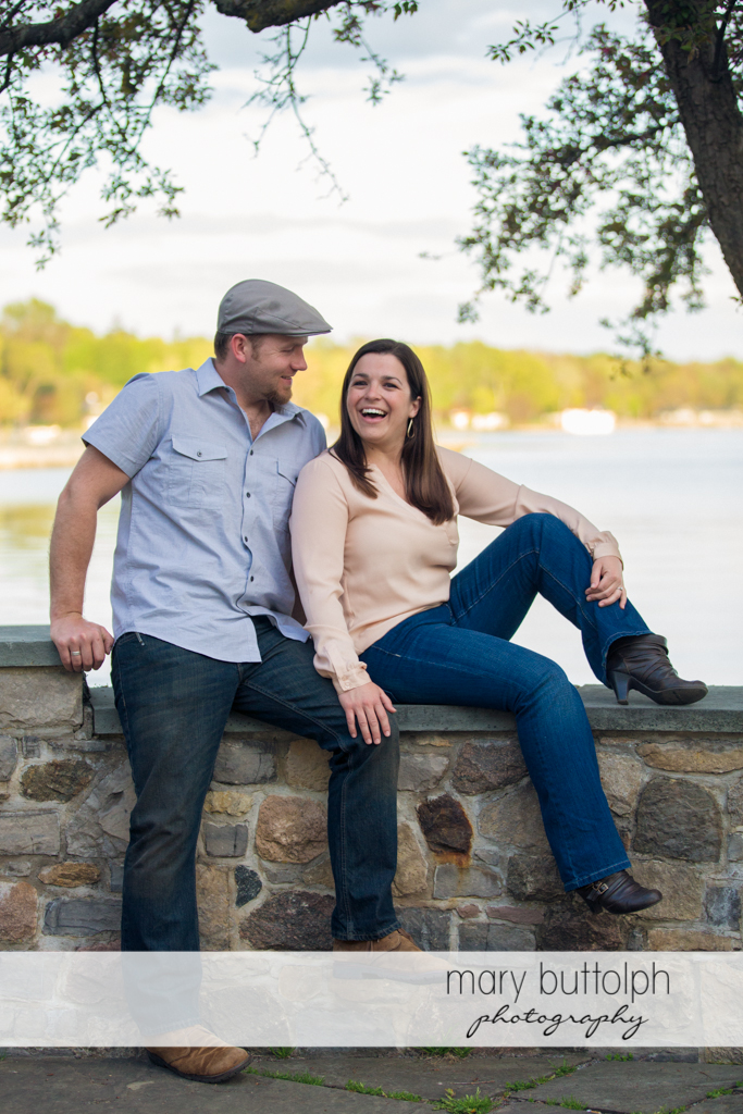 Couple sit on a stone wall near the lake at Skaneateles Engagement
