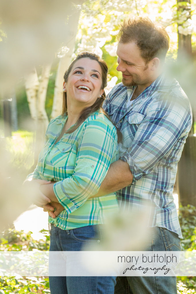Couple share a light moment in the garden at Skaneateles Engagement