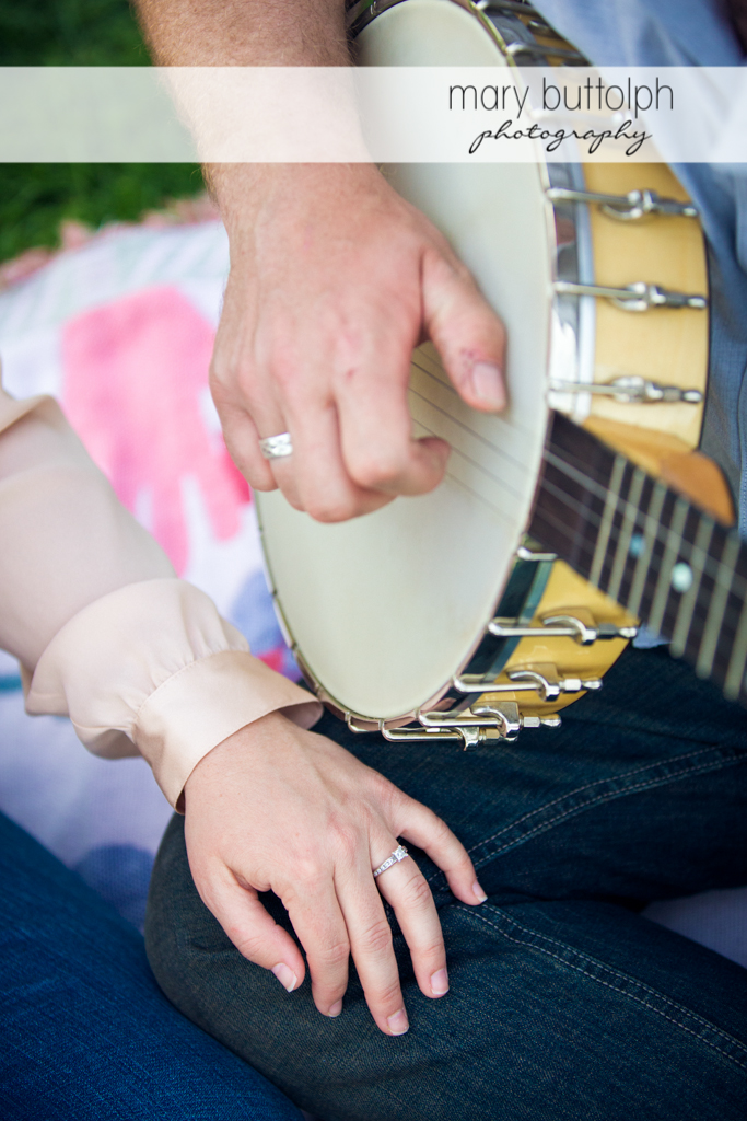 Close up of woman's engagement ring as her companion plays the banjo at Skaneateles Engagement