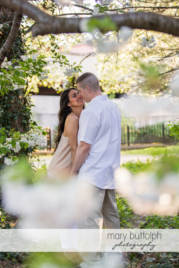 Couple show their affection near the lake at Franklin Square Engagement