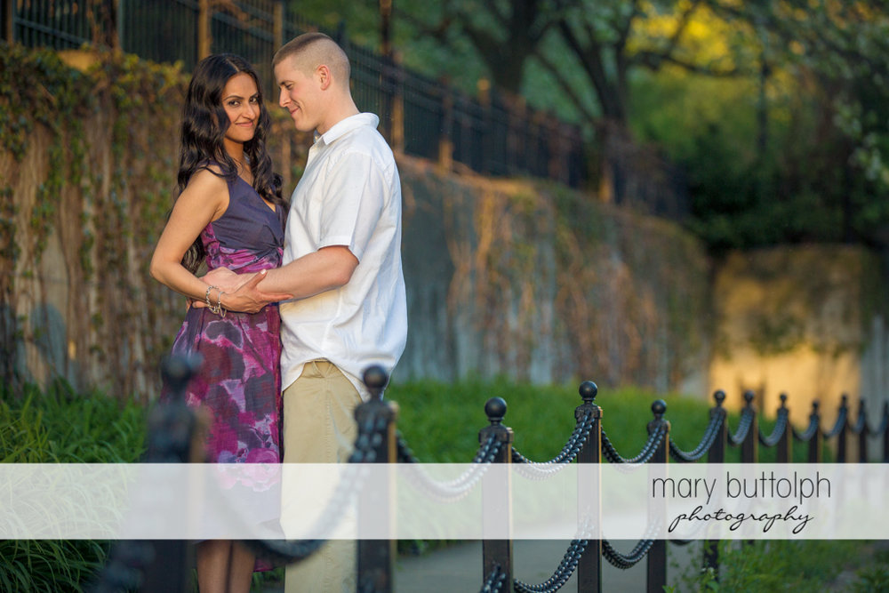 Couple pose for the camera near the fence at Franklin Square Engagement