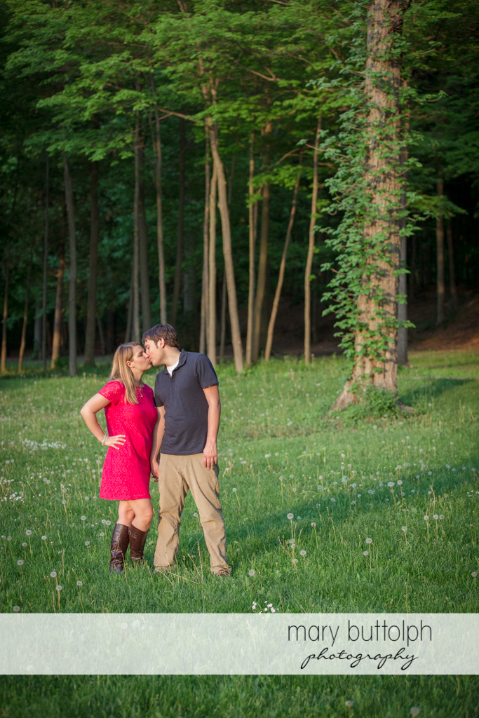 Couple kiss in the woods at Green Lakes State Park Engagement