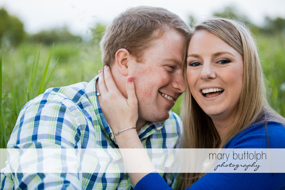 Couple have a good time in the field at Skaneateles Engagement