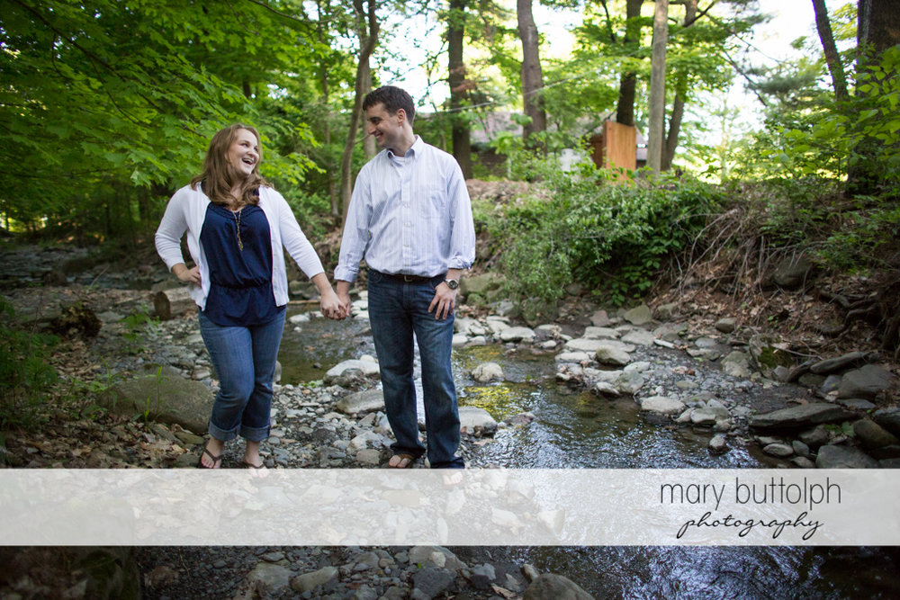 Couple stroll near a creek at Lourdes Camp Engagement