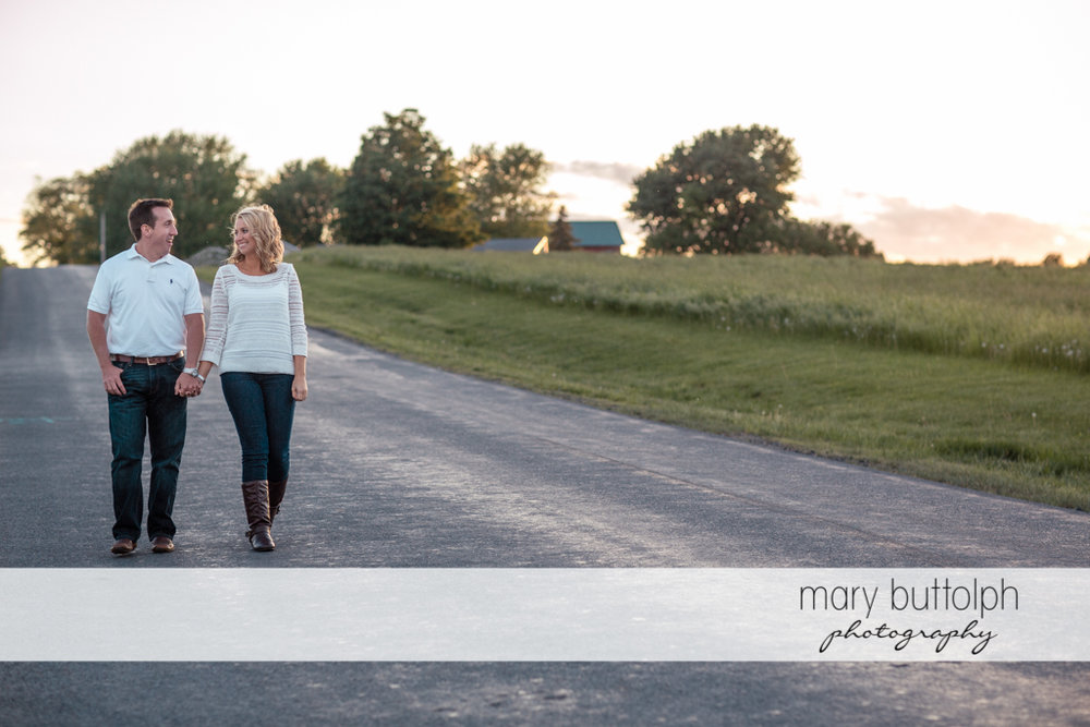 Couple follow the road at Skaneateles Engagement