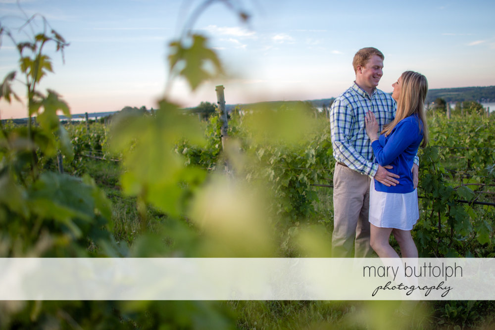 Couple pose near a fence in the field at Skaneateles Engagement