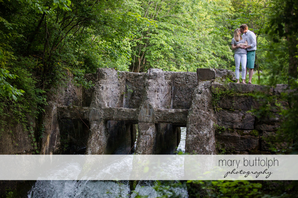 Couple stand on a stone bridge at Skaneateles Engagement