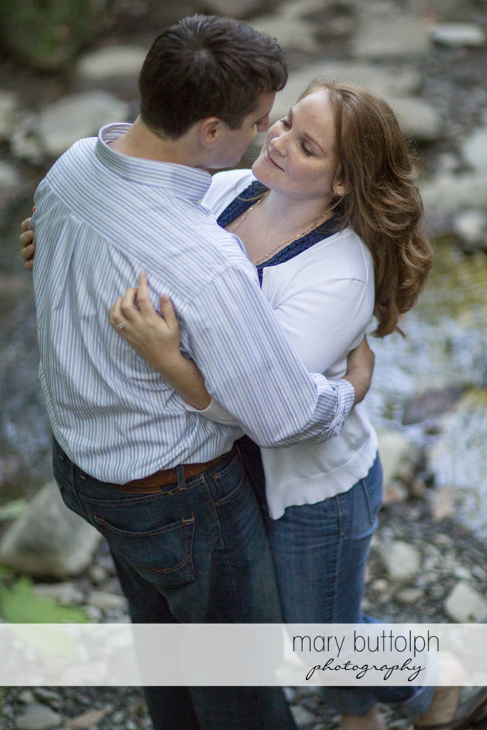 Couple get romantic near a creek at Lourdes Camp Engagement