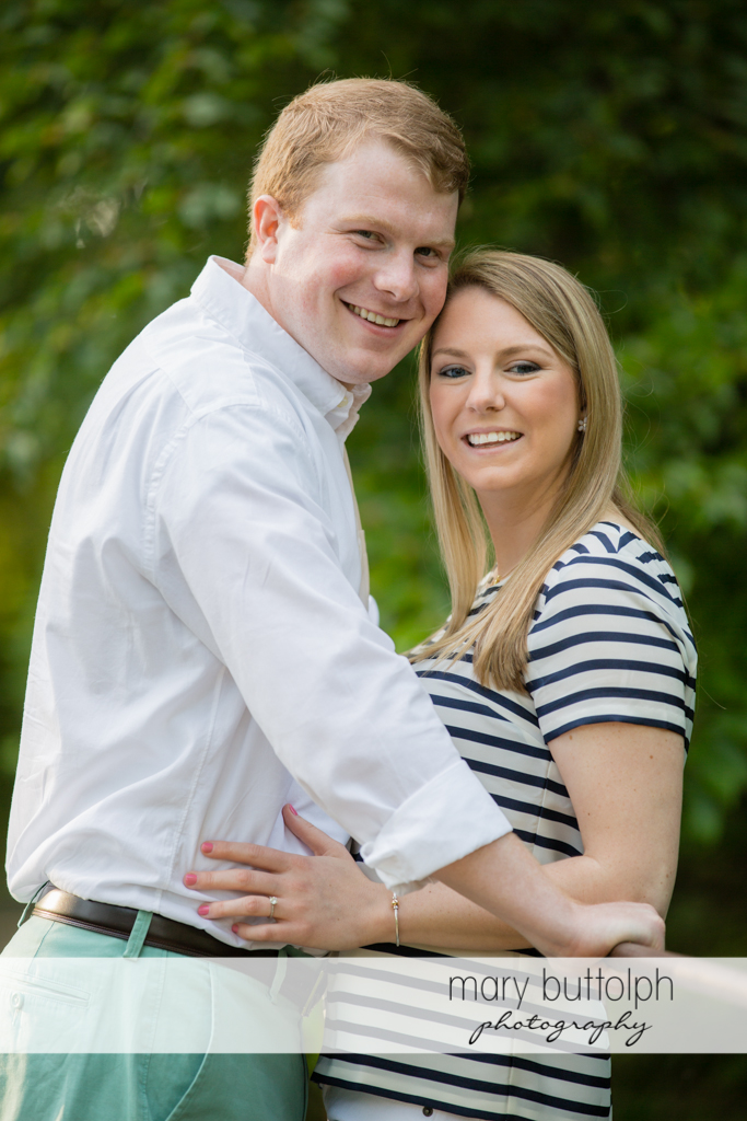 Couple face the camera on the bridge at Skaneateles Engagement