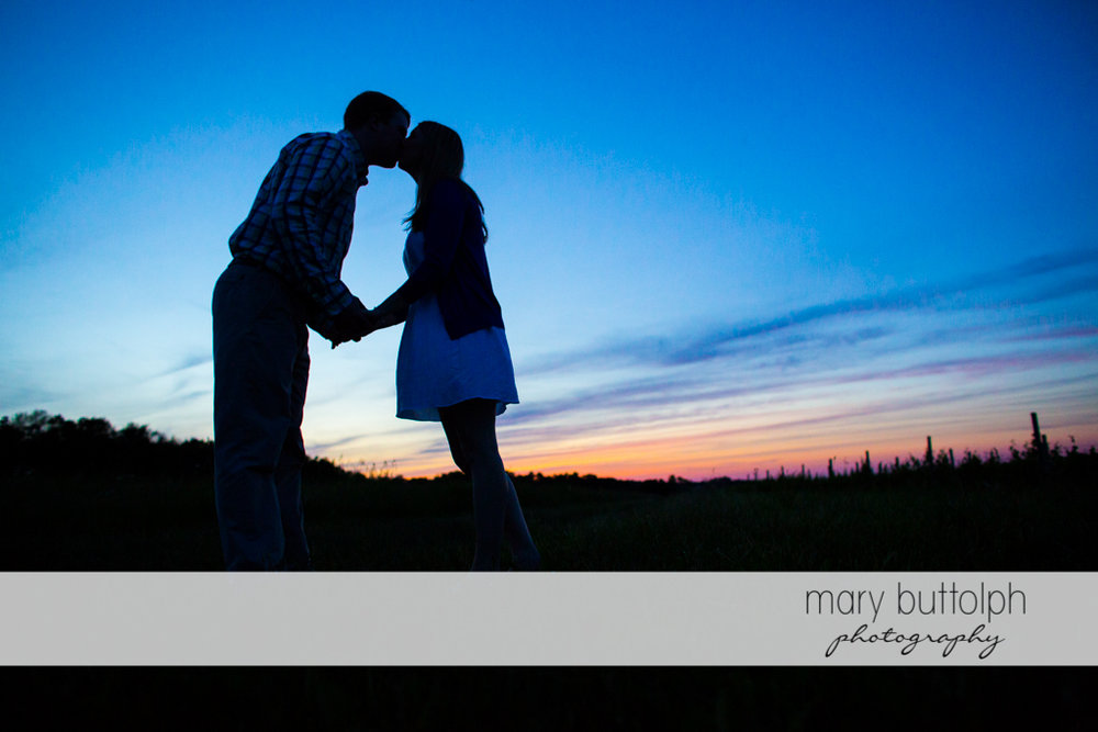 Couple kiss as the sun sets at Skaneateles Engagement