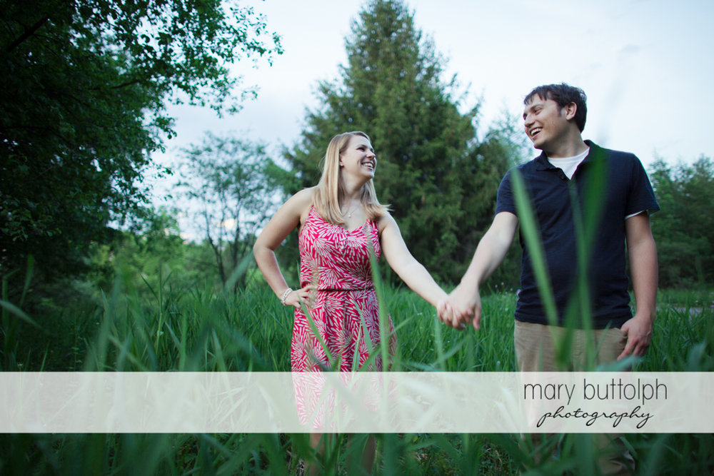 Couple hold hands in the woods at Green Lakes State Park Engagement