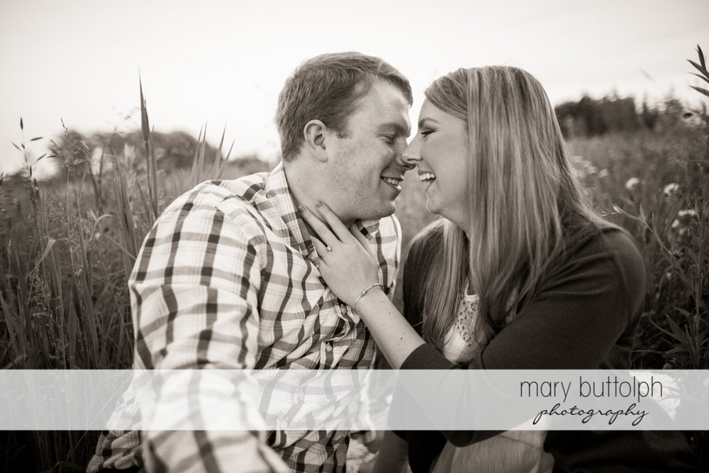 Couple share a laugh in the field at Skaneateles Engagement