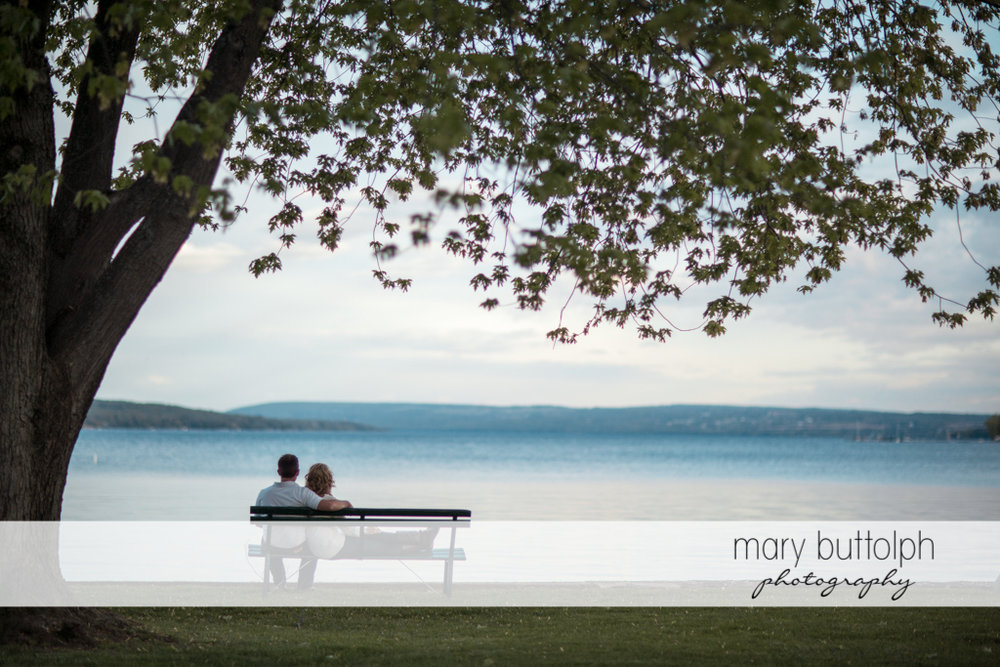 Couple sit in front of the lake at Skaneateles Engagement