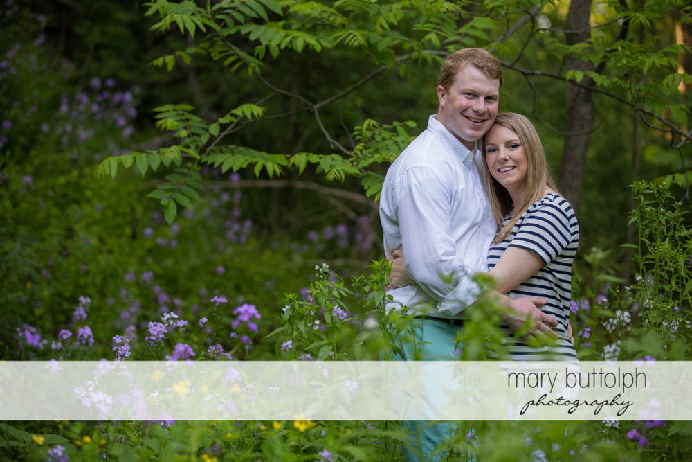 Couple embrace in the garden full of flowers at Skaneatles Engagement