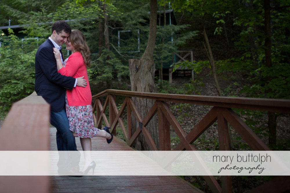 Couple pose on a wooden bridge at Lourdes Camp Engagement