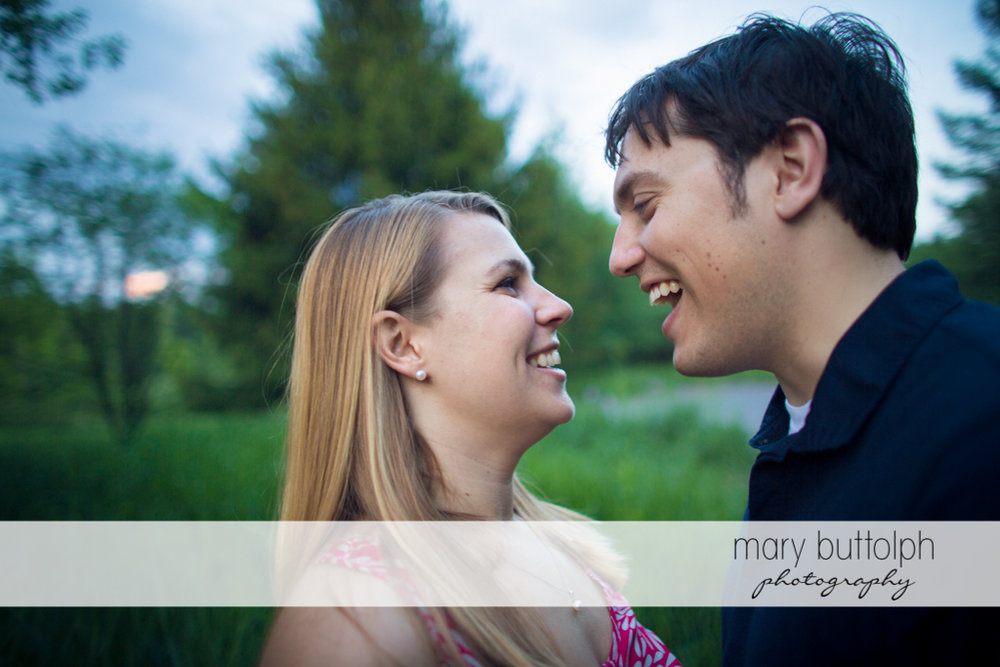 Couple share a laugh in the woods at Green Lakes State Park Engagement