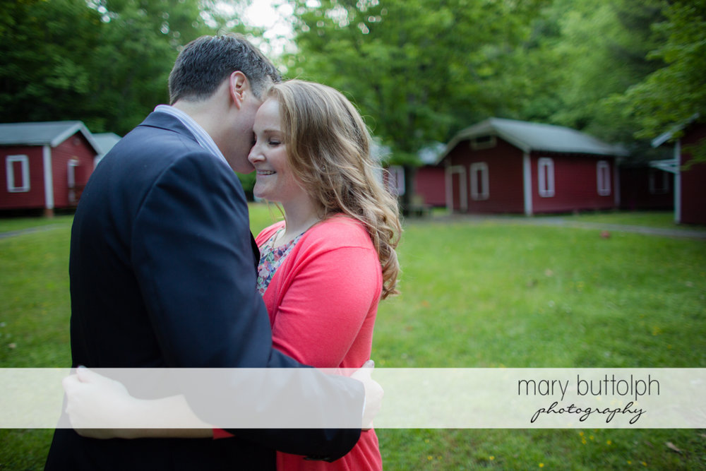 Couple embrace near the cabins at Lourdes Camp Engagement