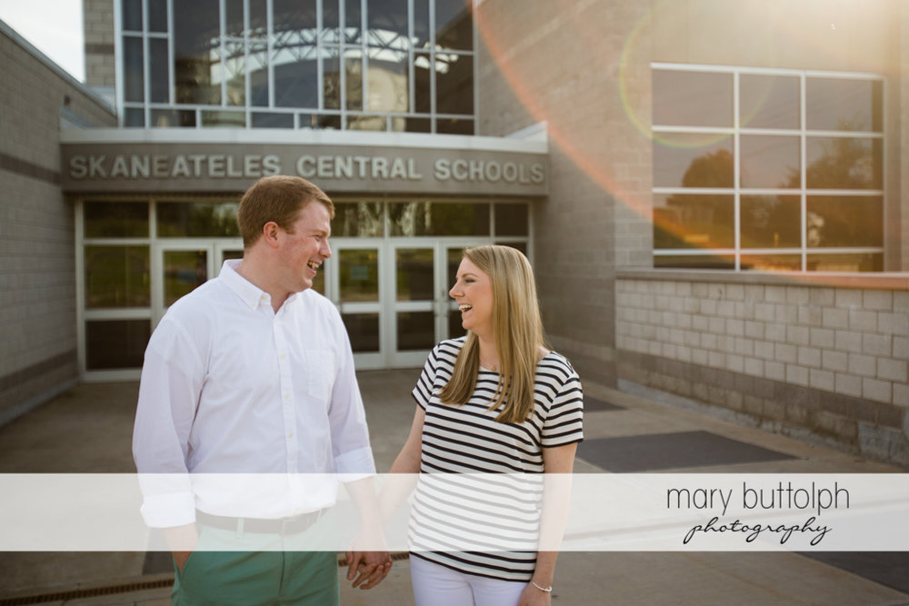 Couple hold hands in front of the school at Skaneateles Engagement