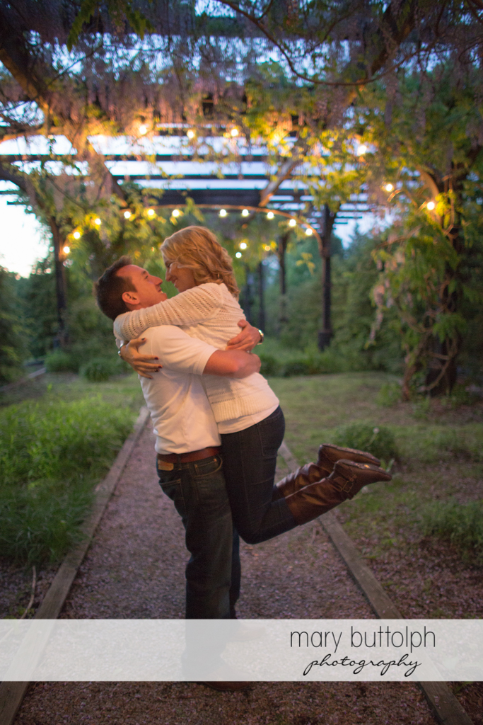 Man lifts woman on the walkway at Skaneateles Engagement