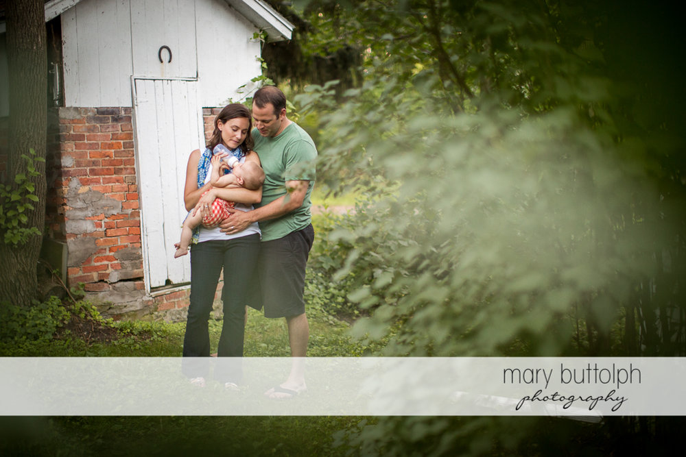 Couple in the backyard with their baby at Skaneateles Family