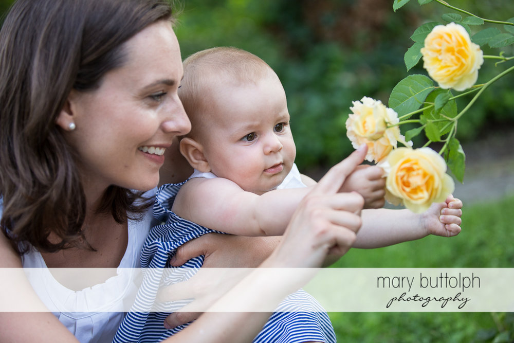 Baby admires the flowers with her mom at Skaneateles Family
