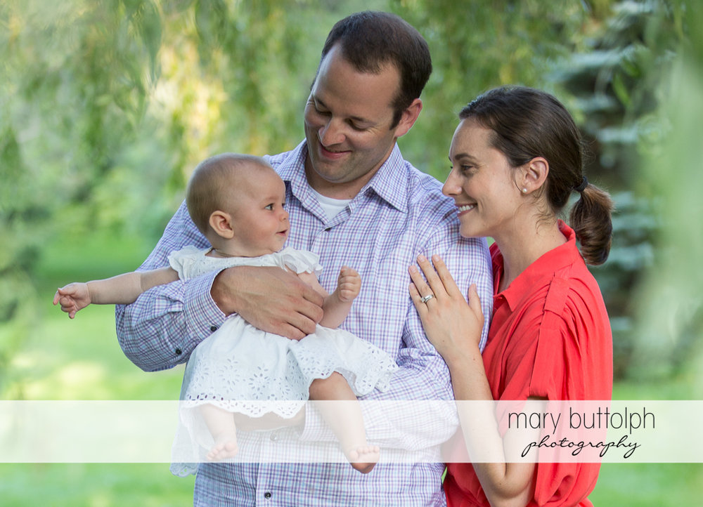 Baby in pretty dress with couple at Skaneateles Famly
