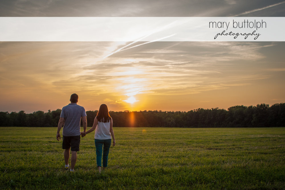 Couple cross the field as they watch the sunset at Skaneateles Lodge at Welch Allyn Engagement