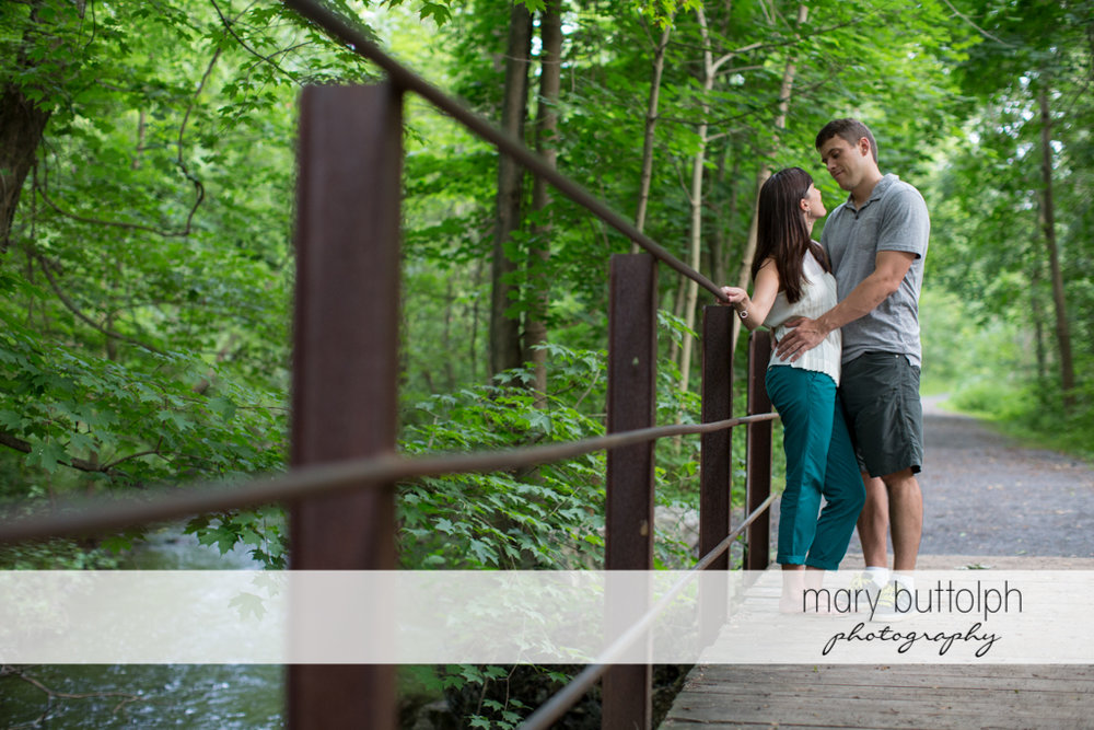 Couple pose near the steel bridge railing at Skaneateles Lodge at Welch Allyn Engagement