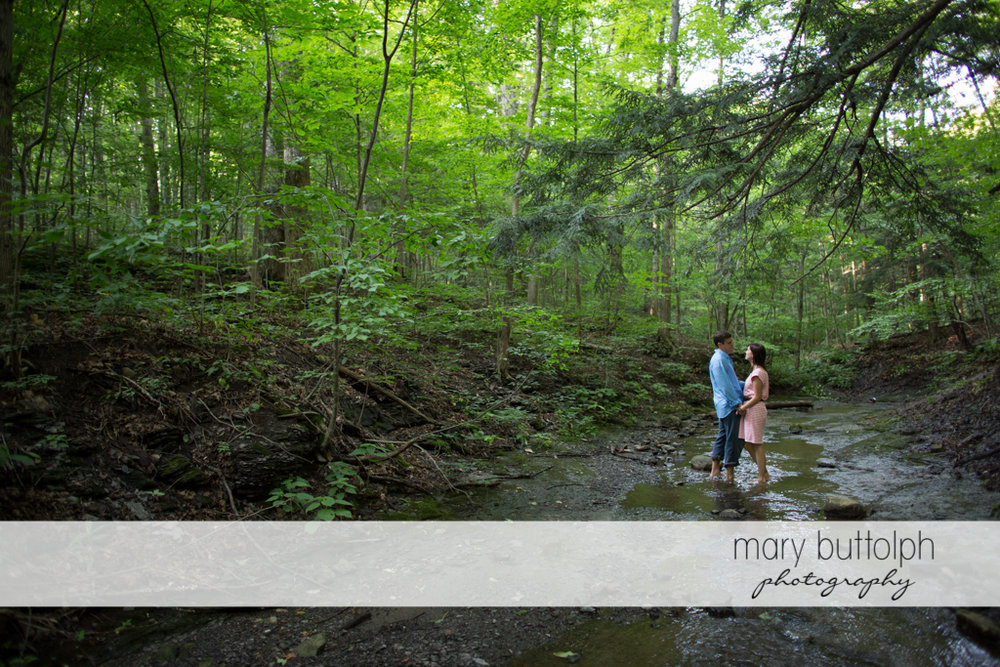 Couple wade in the brook at the woods at Skaneateles Lodge at Welch Allyn Engagement