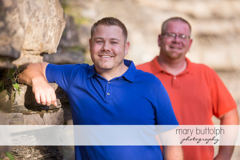 Same sex couple pose near a rock at Salmon River Falls Engagement