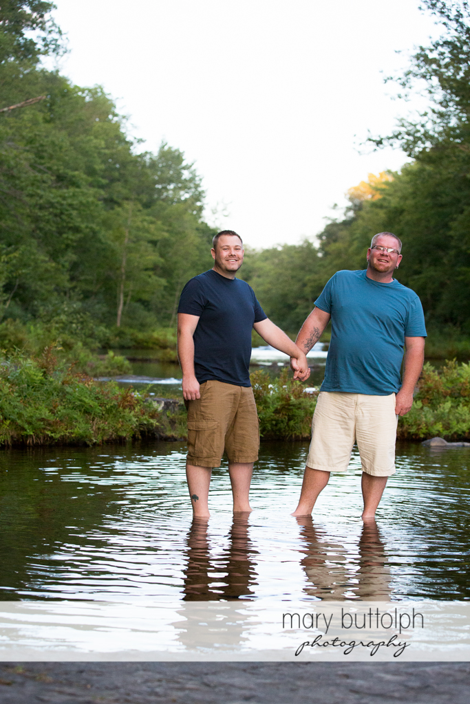 Same sex couple wade in the river at Salmon River Falls Engagement