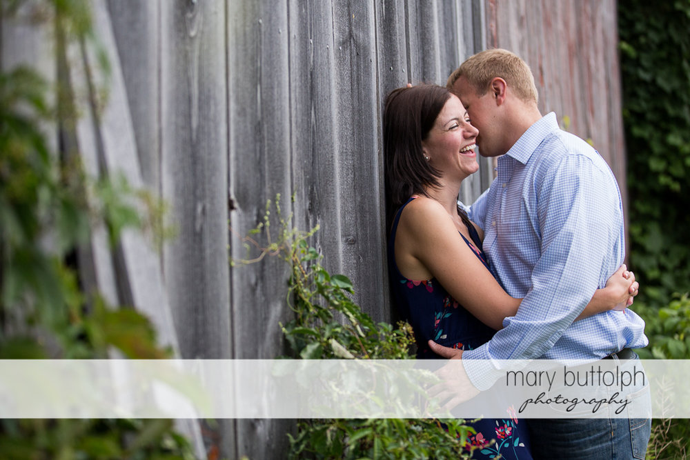 Couple have fun near a wooden structure at Skaneateles Farm Engagement